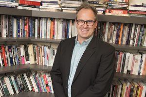 Andrew Hartman standing in front of shelves of books