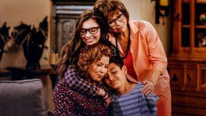 A group hug with a mom, daughter, son, and grandma
