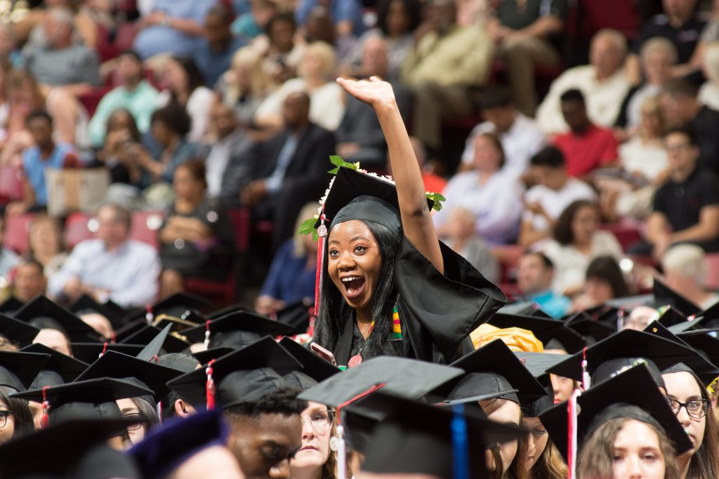 A graduate joyfully waves to someone in the crowd at Commencement