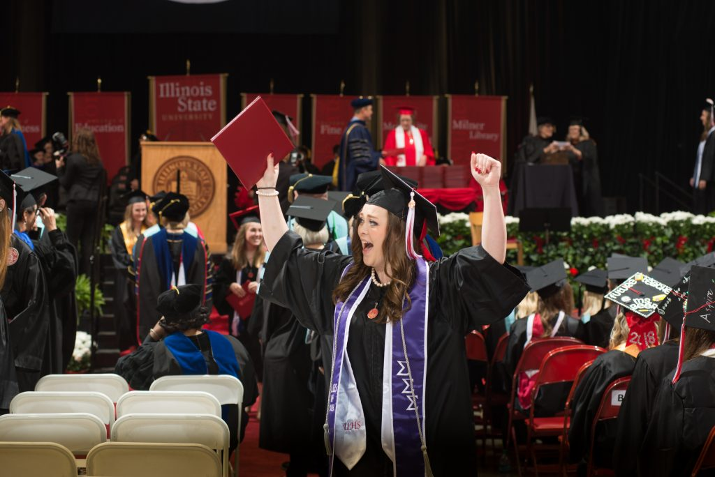 A graduate cheering with her arms in the air at commencement exercises