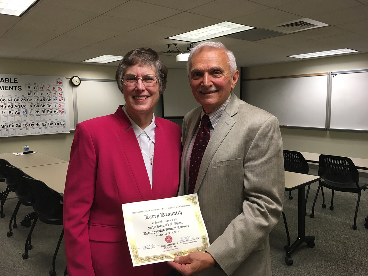 woman and man standing together in a classroom with the man holding a certificate
