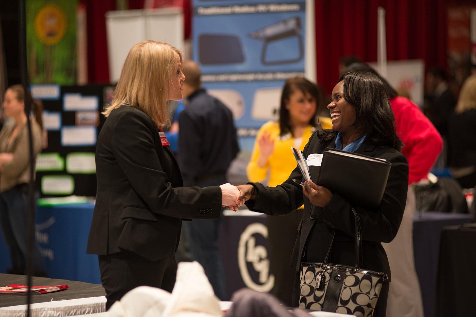 A student talks to a prospective employer at a Career Center job fair
