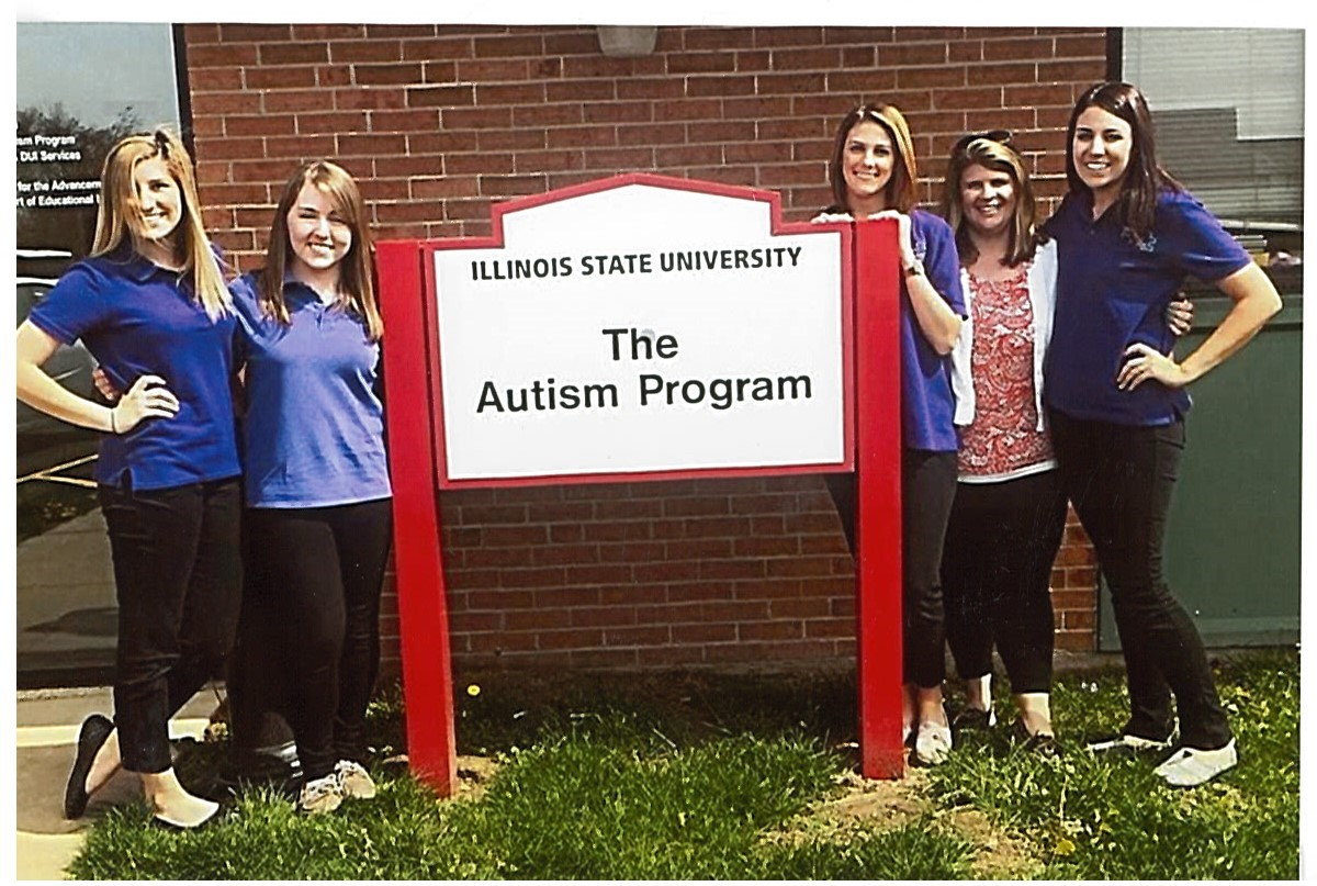 4 graduate students and 1 instructor stand next to a sign for Illinois State University The Autism Program