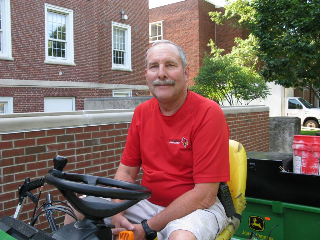 Tom Cotton, seated on his John Deere tractor on a sidewalk outside Hovey Hall