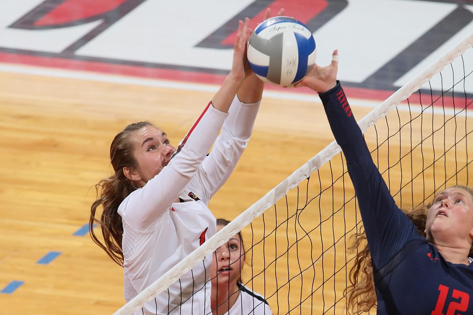 volleyball player blocks ball at net