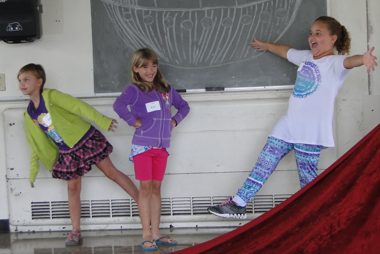 Three children performing during a Saturday Morning Creative Drama class.