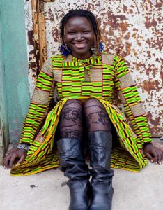 woman sitting o the street and smiling