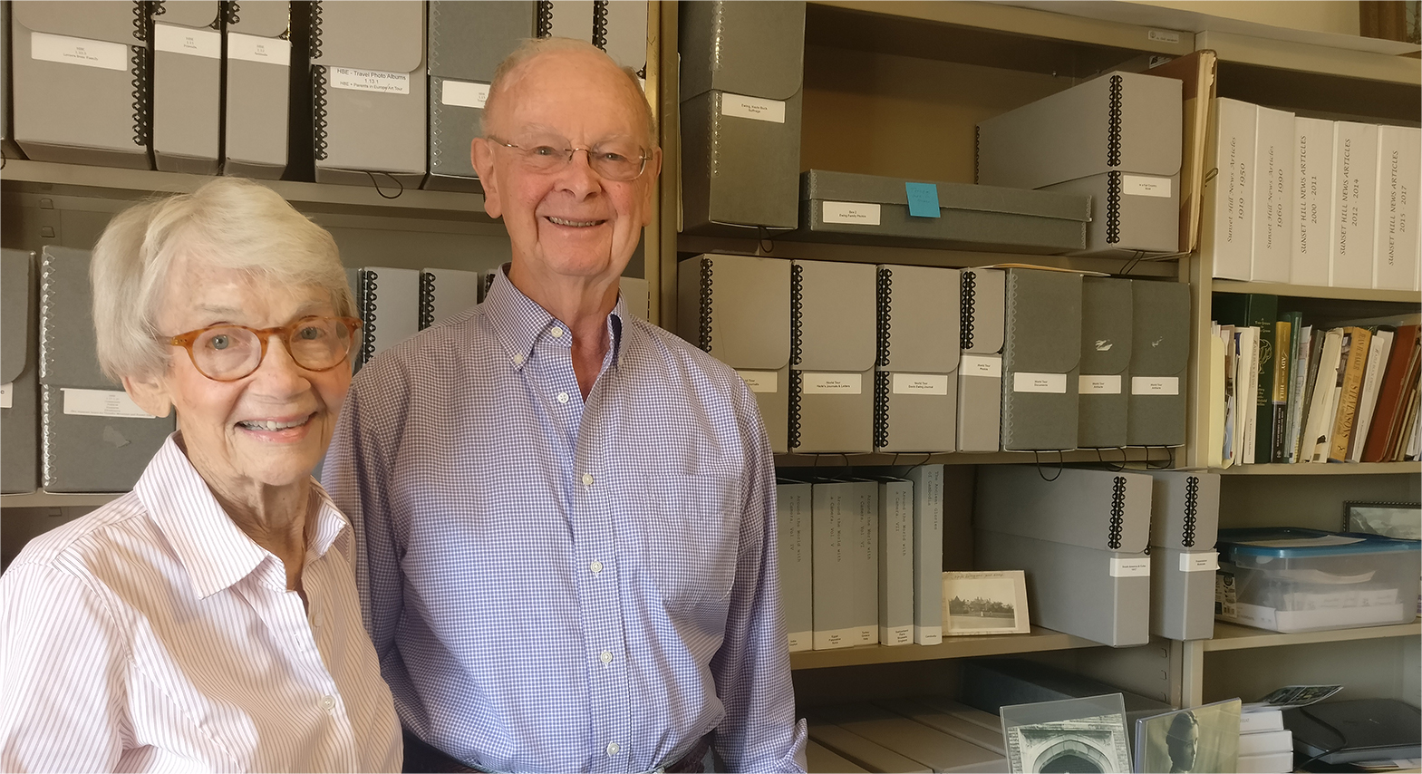 A man and woman standing in front of shelves of archive boxes