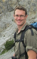 Man with a backpack with a rock formation in the background