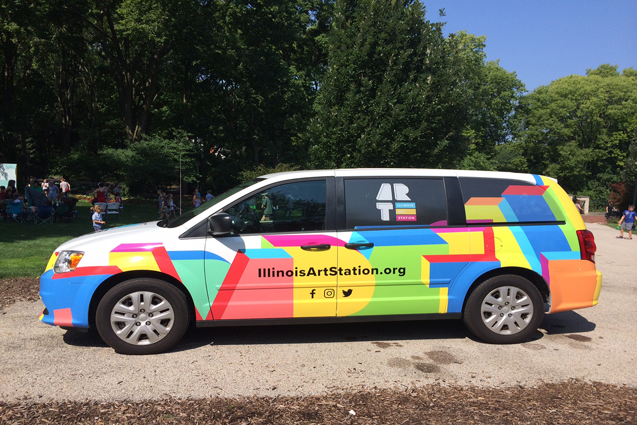 """Colorful minivan with """"Illinois Art Station"""" written along the side."""