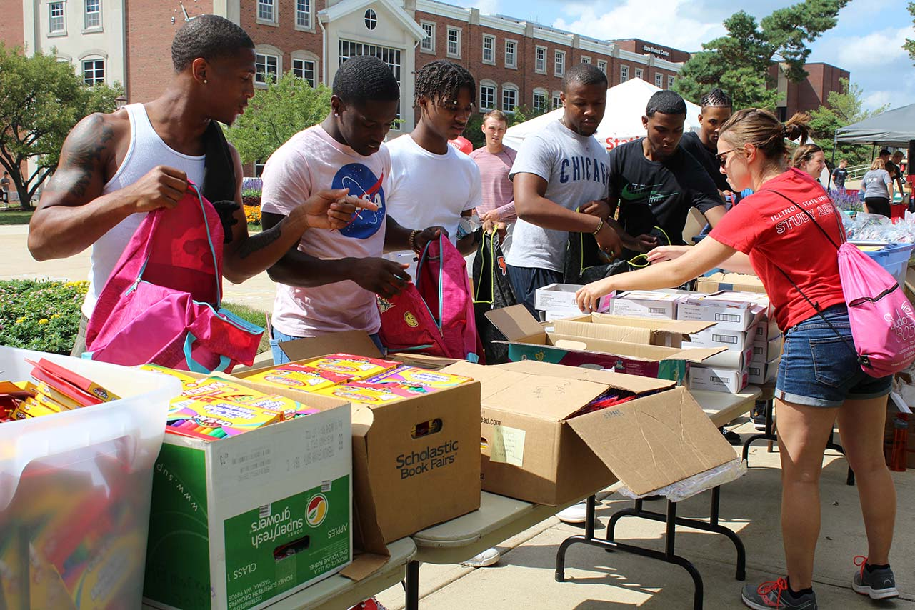 line of students packing books into backpacks.