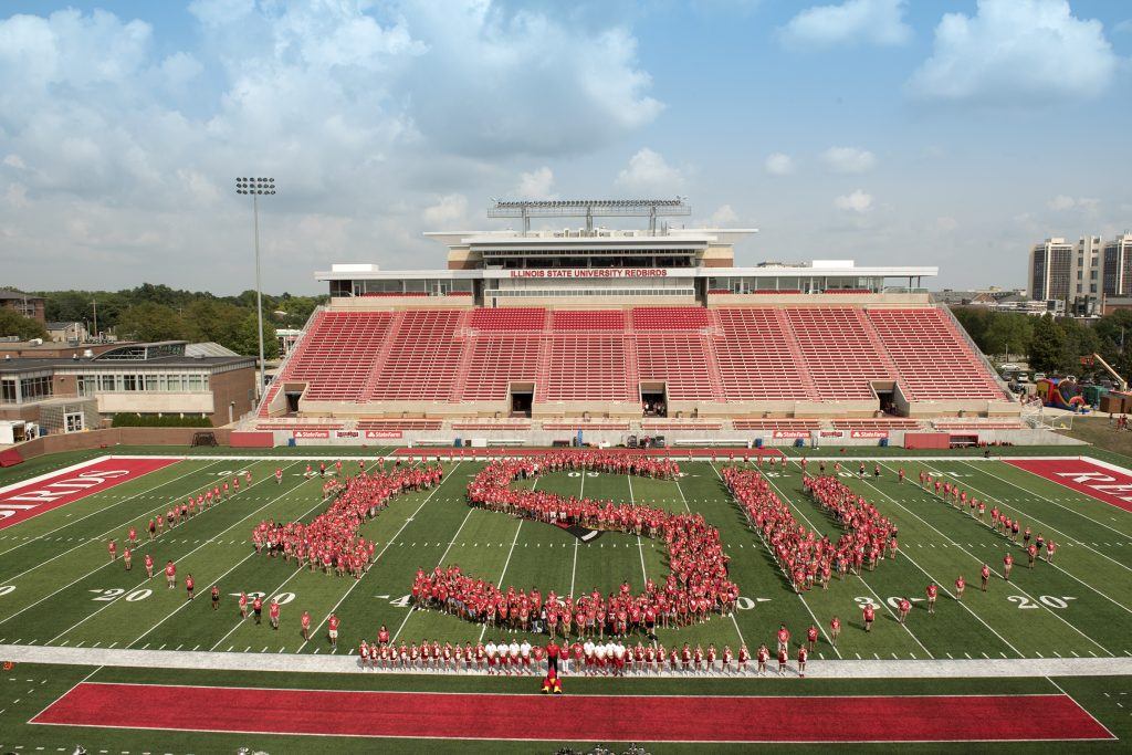 Group of students form the letters 'ISU' on the football field