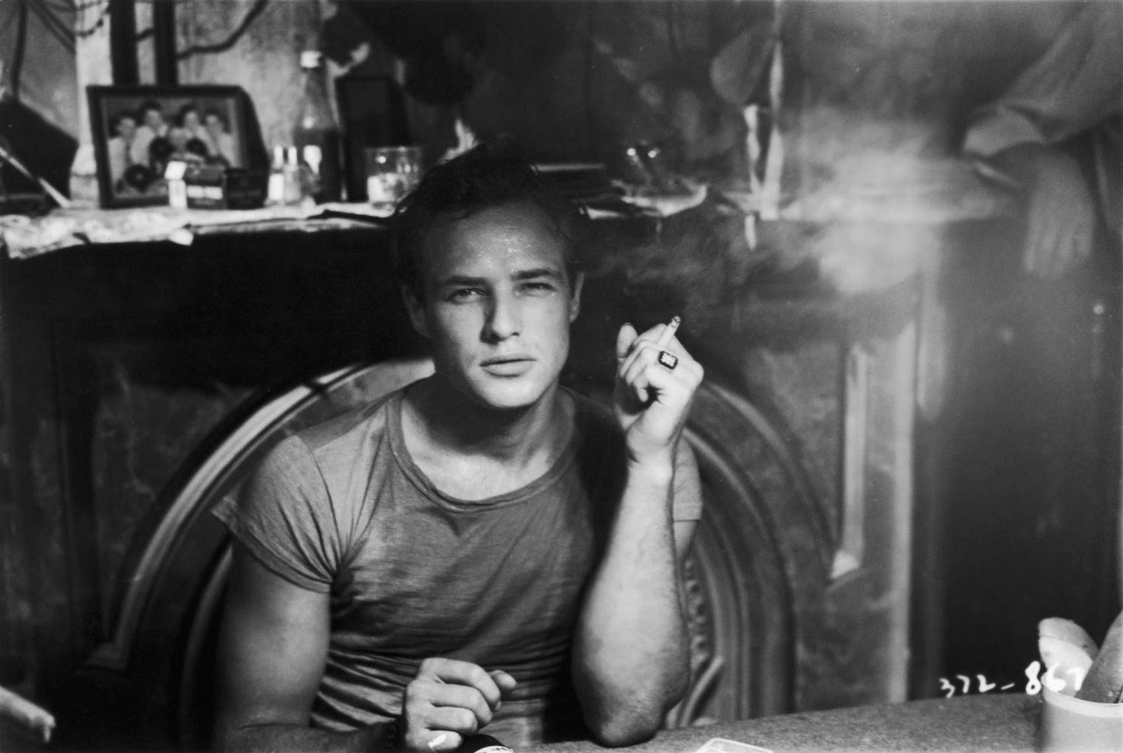 man sitting and smoking a cigarette with the smoke wafting around him,