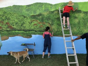 Two women painting a mural