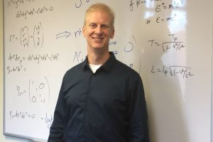 Professor Neil Christensen standing in front of board with equations on it