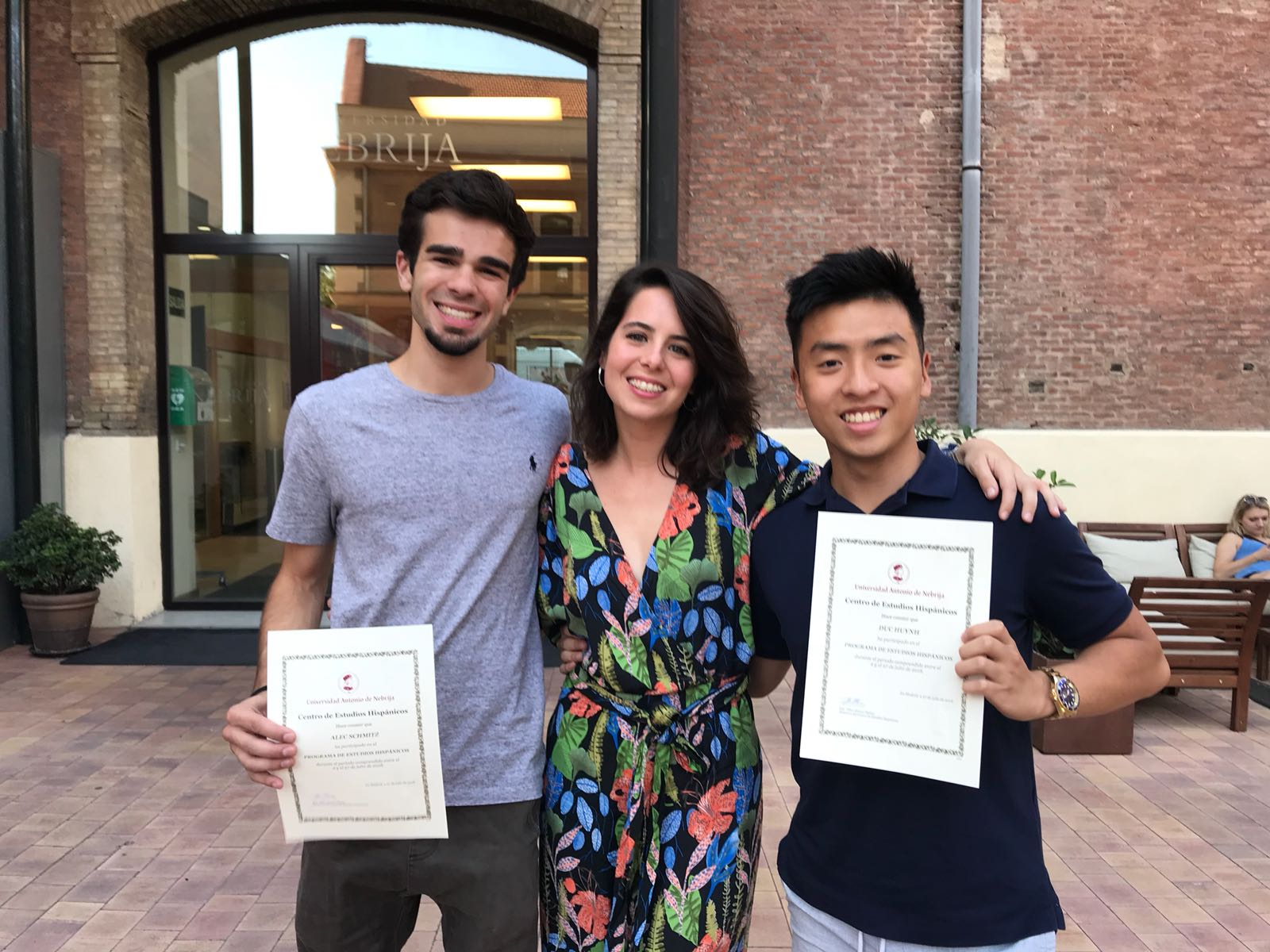 Three people standing outside, two holding up pieces of paper