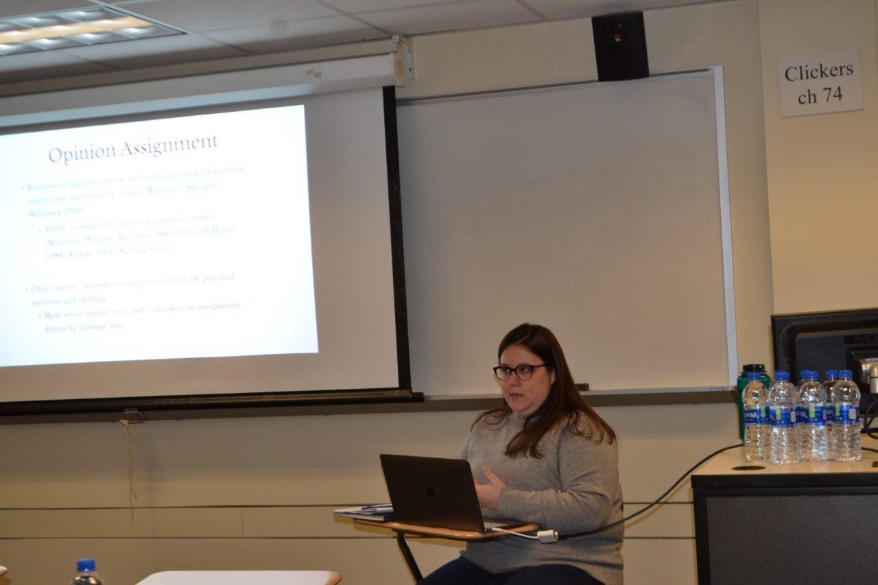 Dr. Leonard sitting in front of lecture slide