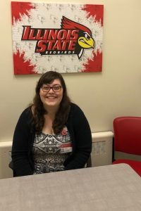 Graduate clinician seated in front of Illinois State wall art in the Speech and Hearing Clinic