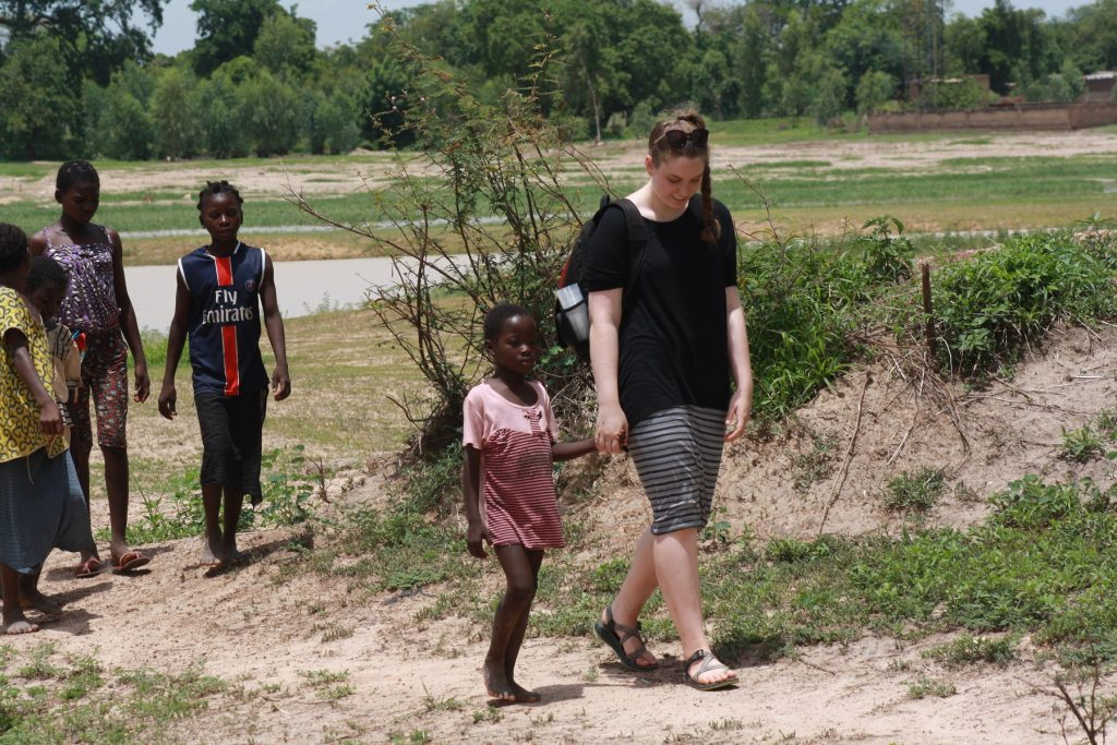 Abby Mustread, ISU Bone Scholar, walks with group of children in Africa.
