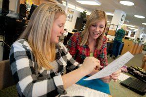 College students look over paperwork.