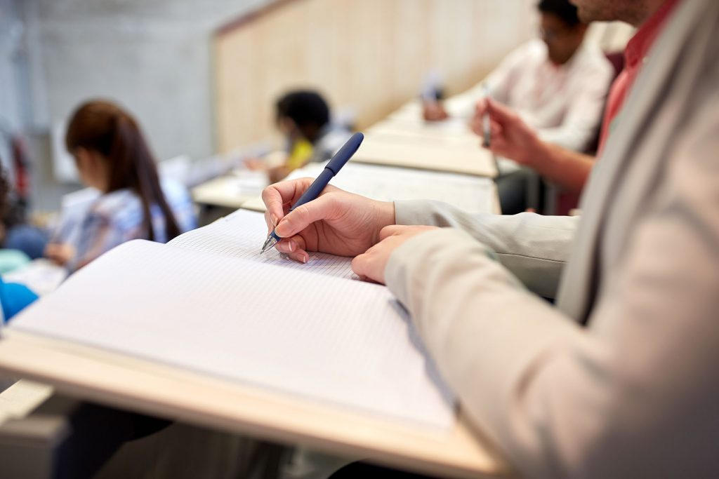 image of a nursing student taking notes in a classroom