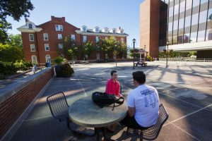 Two students sit and talk on Illinois State University's Quad.