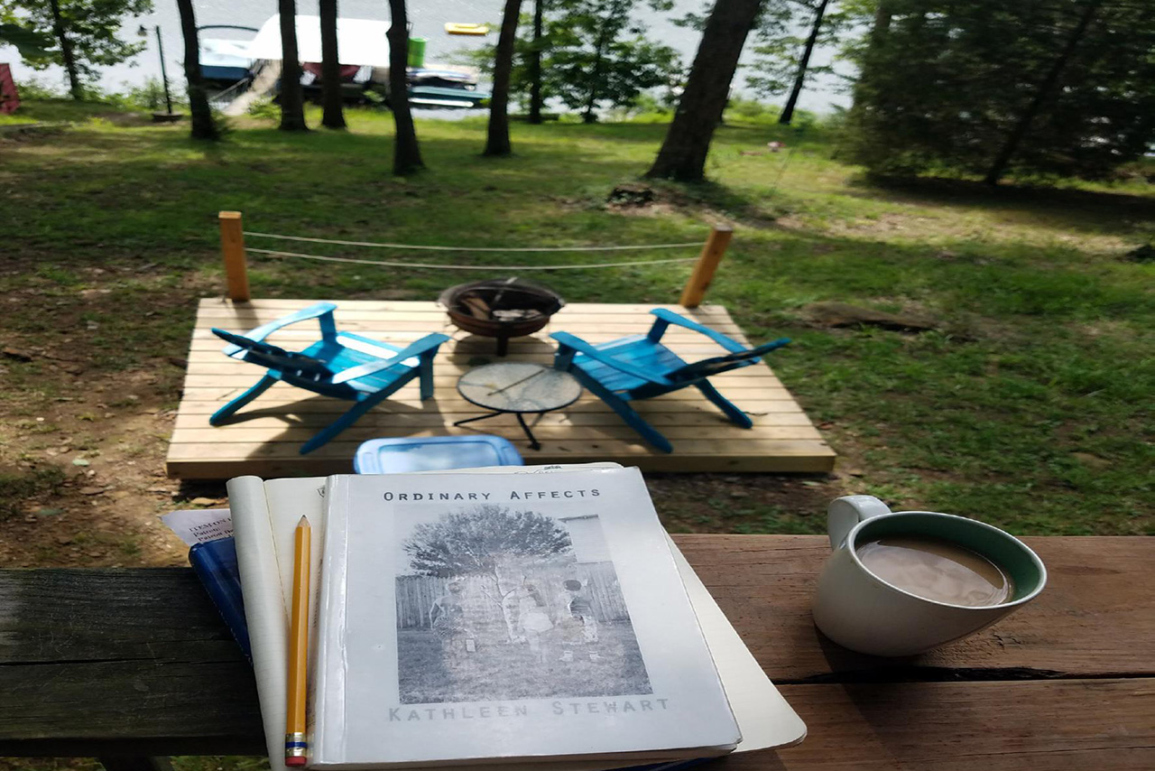 Image taken during the residency of the lake, a boat dock, a patio with a fire pit, books about art, and a coffee mug.