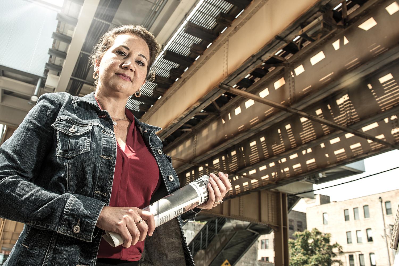 Marlen Garcia under L tracks in Chicago holding newspaper