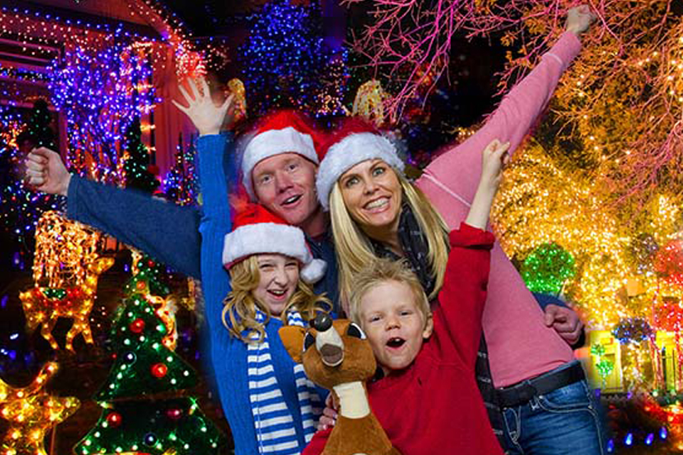 Family cheering in front of Christmas lights