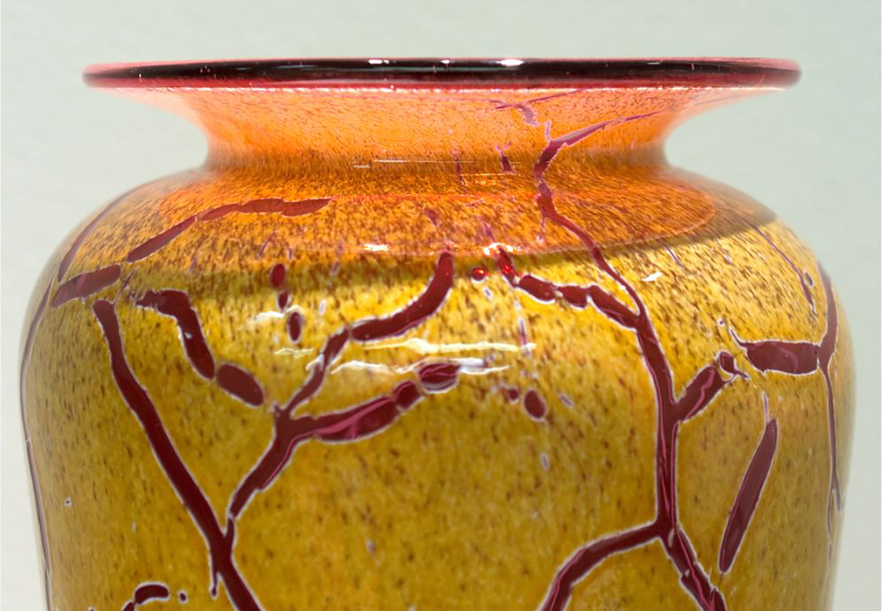 glass vase with vines of color cutting through a speckled base