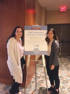 Two women in front of research poster board