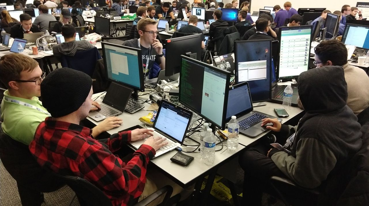 a room full of people at laptops and computers.