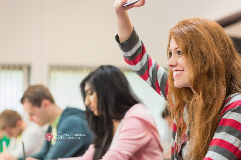 Students in class, one with hand raised