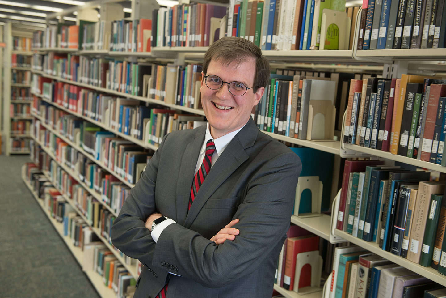 image of Paul Unsbee standing in front of the stacks at Milner Library