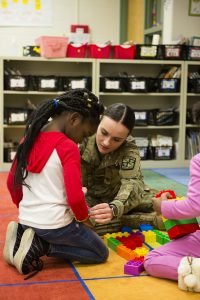 Cadet Isabella Diez, a junior at Illinois State, helps one of her first grader friends with a bracelet during the ROTC's weekly Cadets Helping Kids visit at Unit 5's Fox Creek Elementary School in Bloomington.
