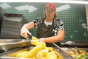 Food worker serves corn