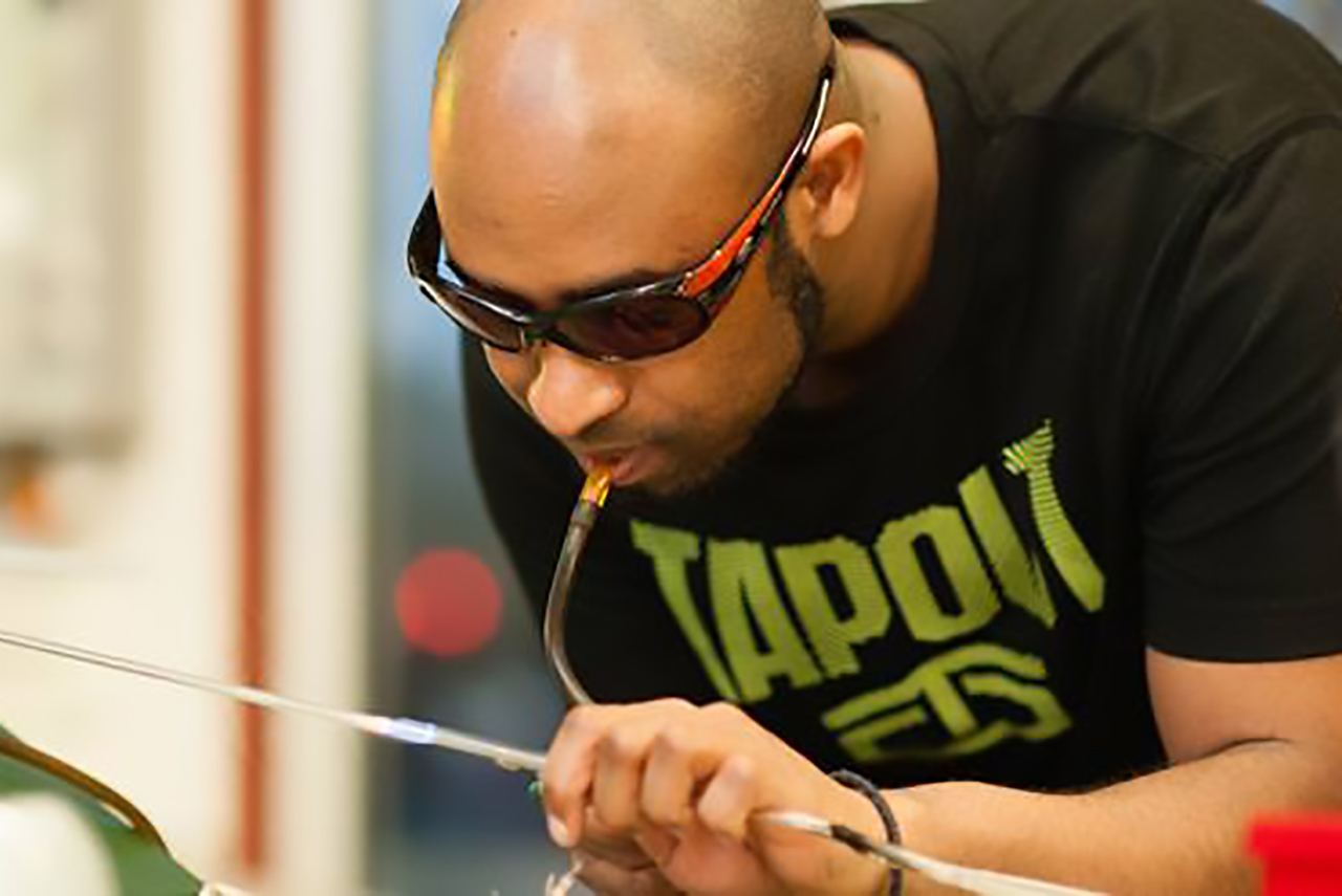 Image of Percy Echols II blowing glass.