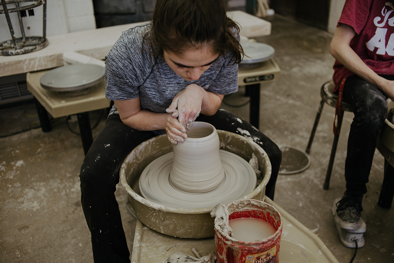 Image of a student working on a ceramic wheel.