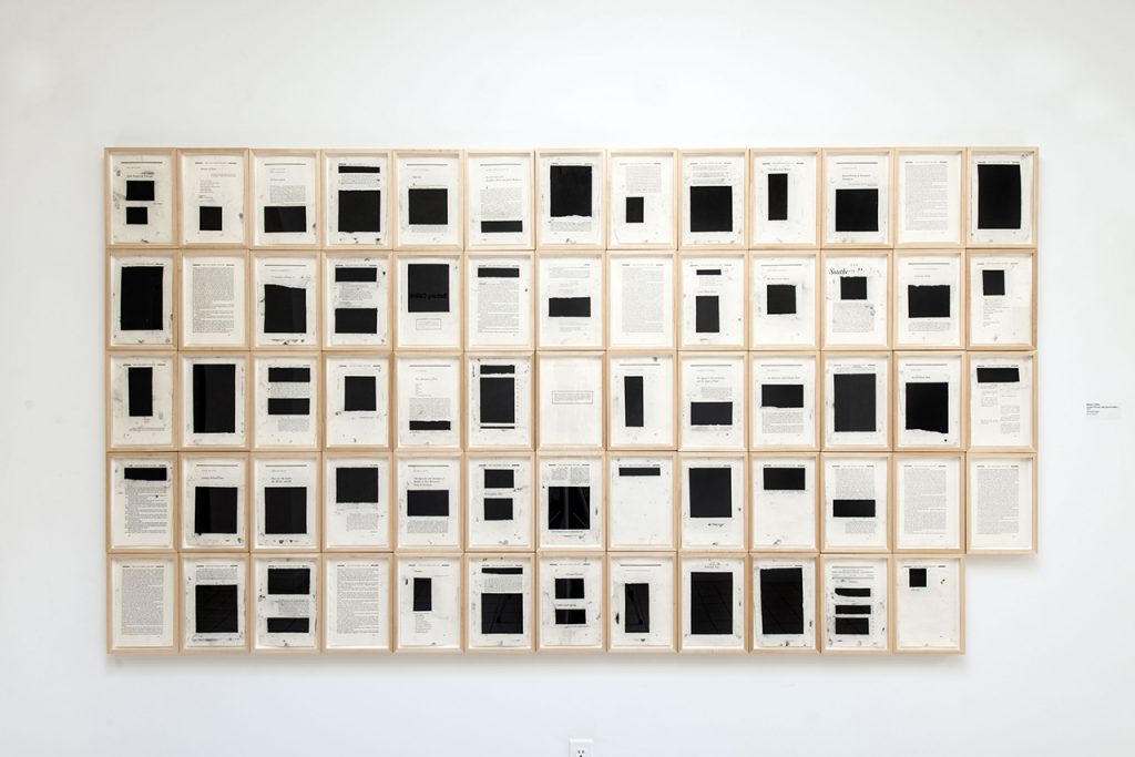 Artwork by Bethany Collins. An edition of the Southern Review that has been dismantled and displayed. Pages are filled with blocks of black covering the text.