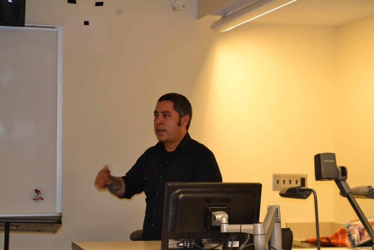 Jason De Leon giving a lecture by desk in a classroom