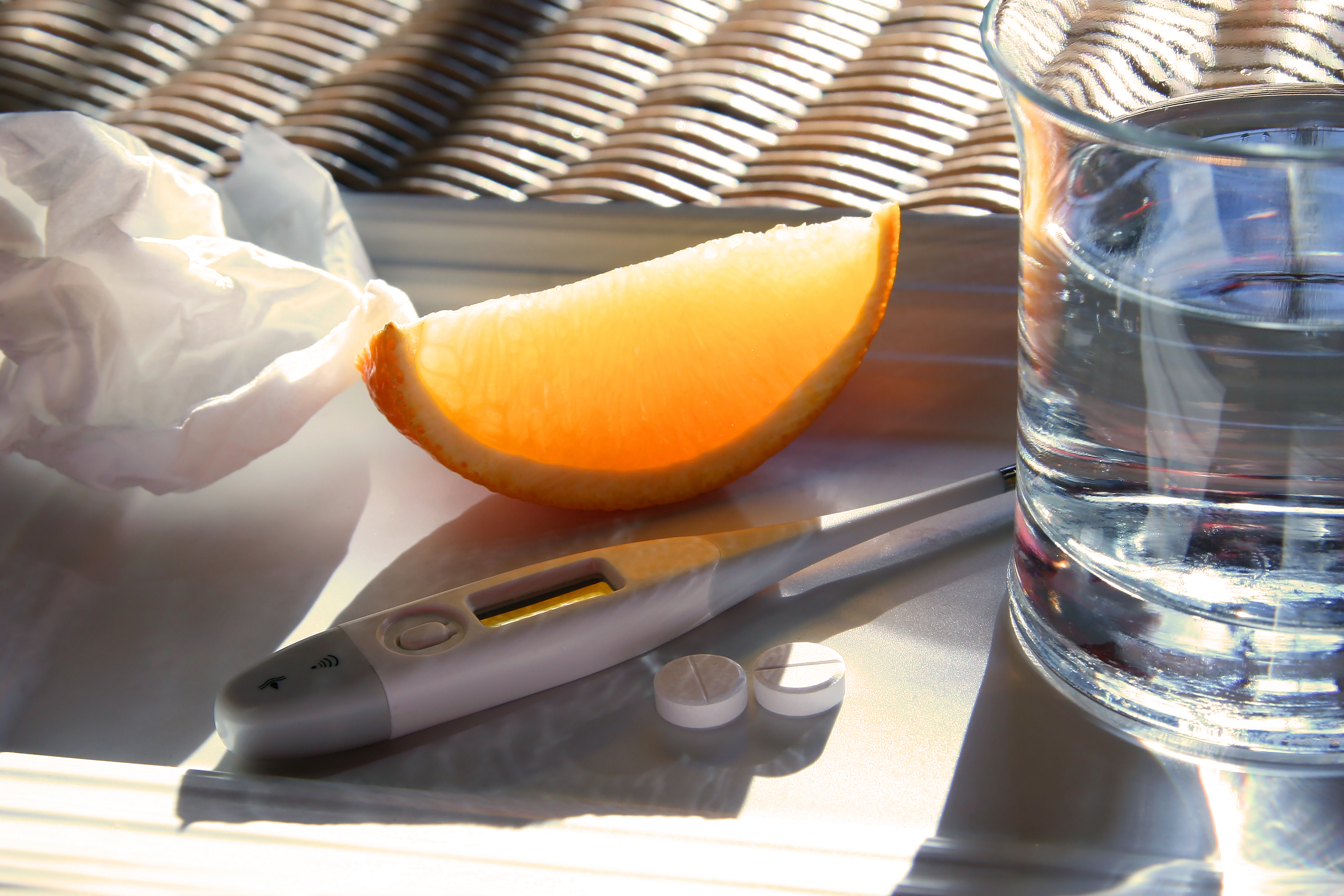 Tissue, orange wedge,water glass, thermometer and cold pills for relief of flu symptoms