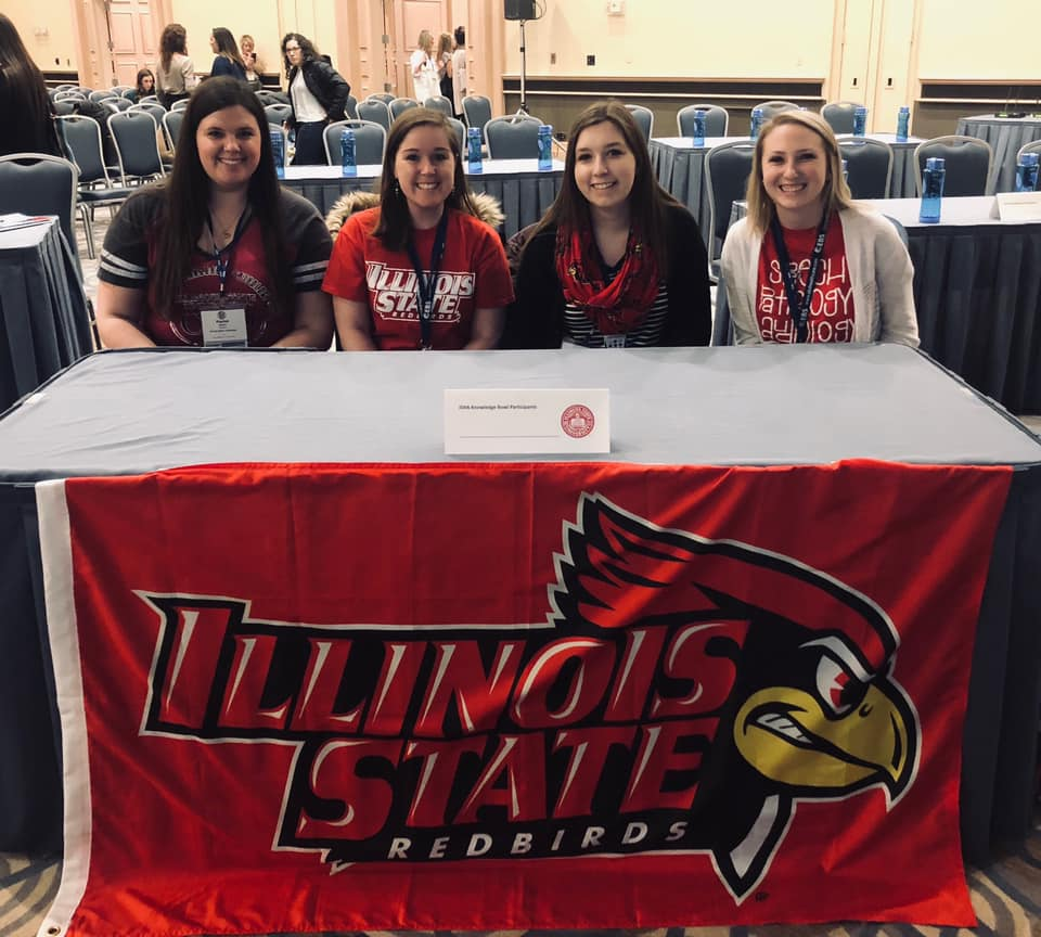 Illinois State's team at the 10th Annual College Bowl. sitting at a table with a Illinois State branded cloth.