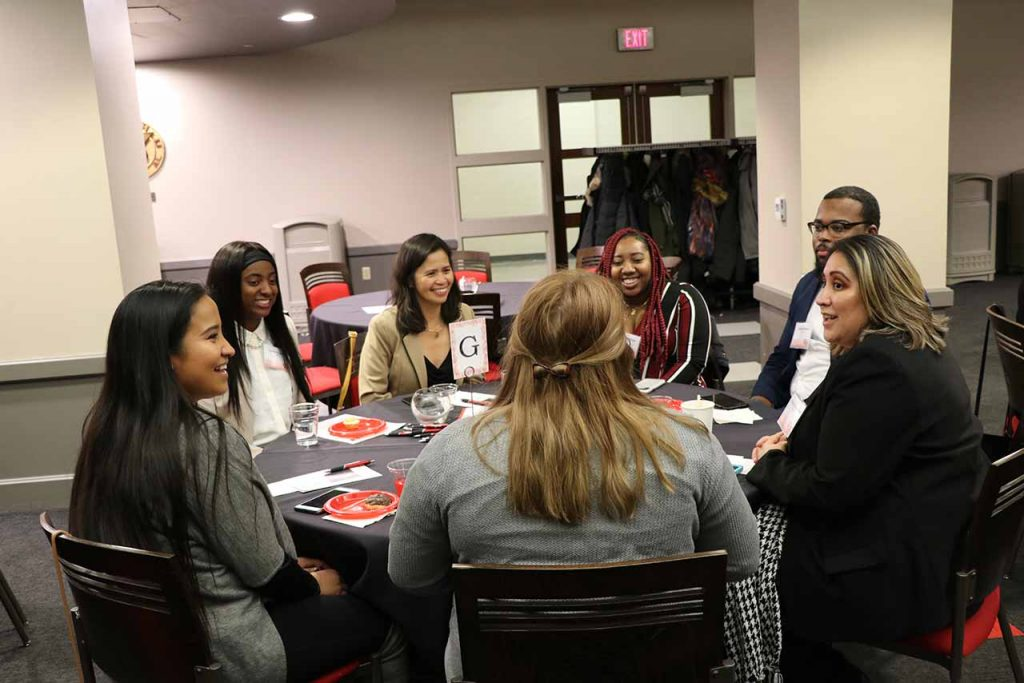 Participants of the On Common Grounds event engage in discussion at their table.