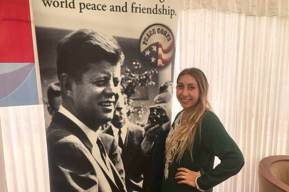 Palecek posing with Peace Corps poster