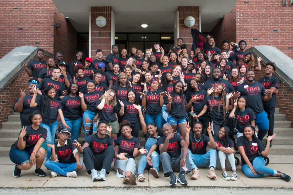 A group of students posing on the steps of Stephenson Hall, wearing shirts with TRIO on them.