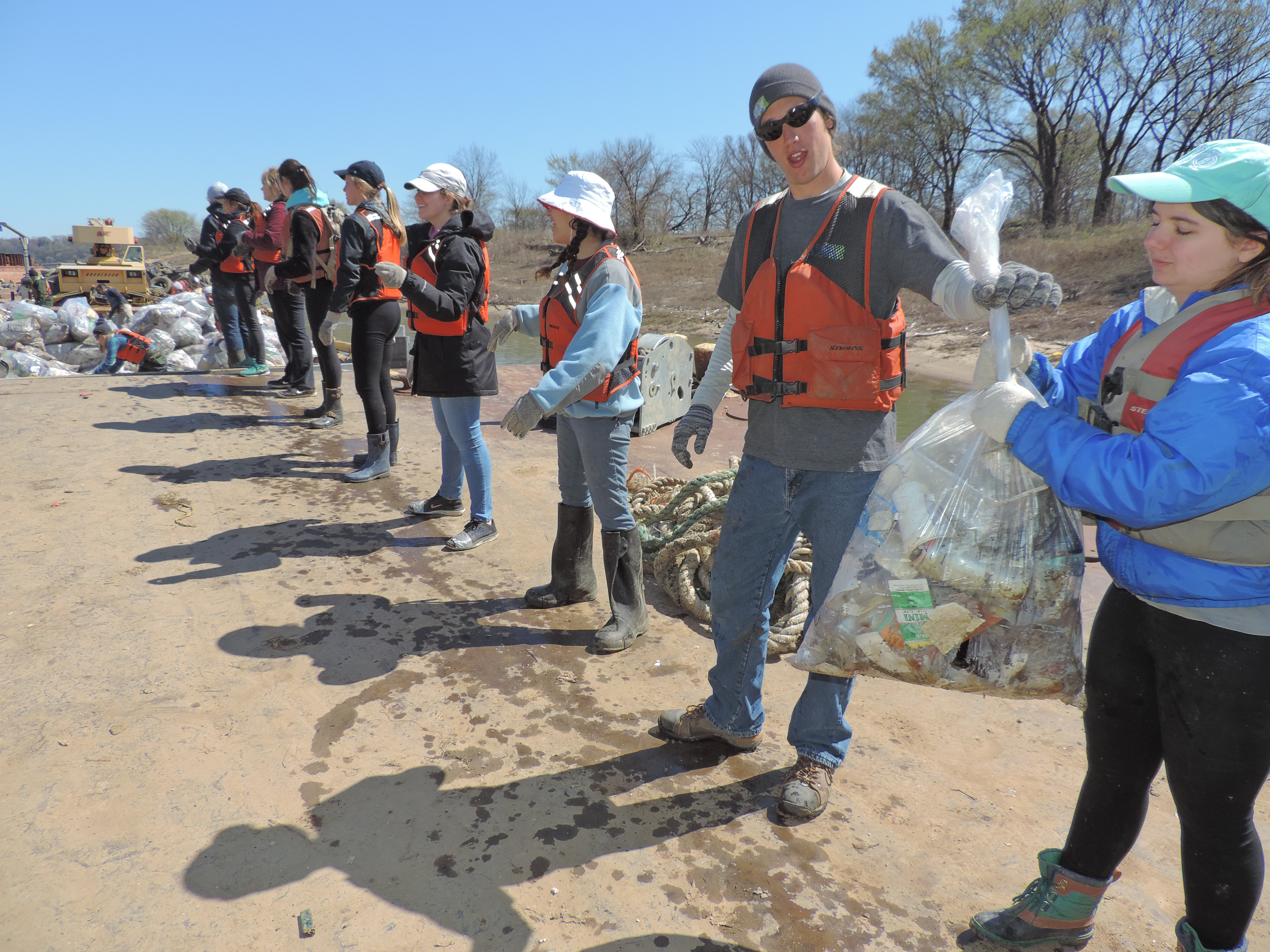 students in a line with bags of trash on Alternative Break