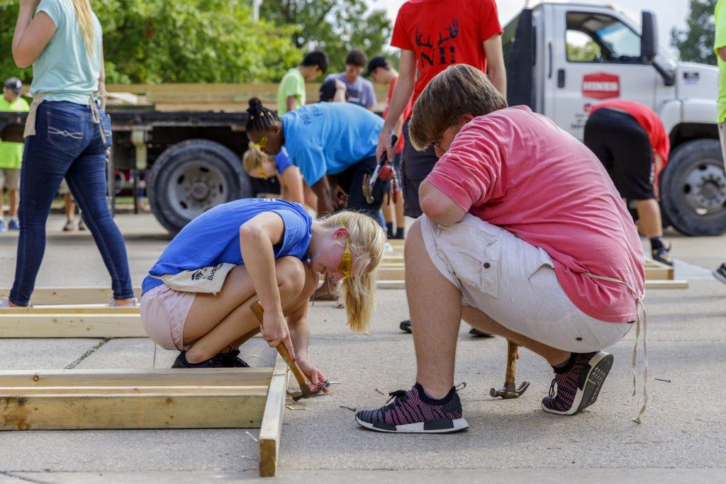 Male and female volunteers hammering wood