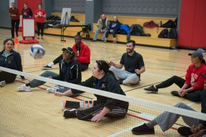 Paralympian Ashley Green shows ISU students how to play sitting volleyball.