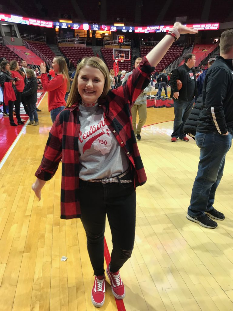 Freshman Redbird girl poses on basketball court at Redbird Arena