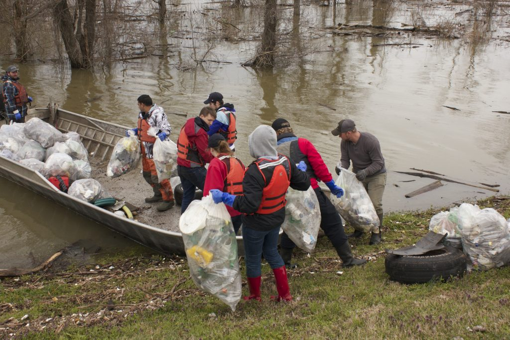 Finishing up at this site, students help load trash onto a boat that will eventually take it to the landfill.